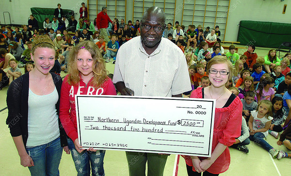 Foothgills leadership students present a cheque for $2,500 to purchase a well in Northern Uganda. Left to right Madison Hill, 13, Grade 7, Ashley Robson, 13, Grade 7, Dr. Chris Opio and Courtney Knutsson, 13, Grade 7. The school has been fundraising all year to raise the money for the well project. Citizen photo by Brent Braaten         May 30 2011
