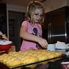 Mara adds sprinkles to pumpkin rolls