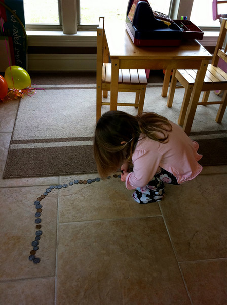 Making a trail on the floor with her play money..?