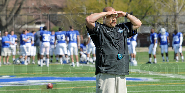 Shade: Indiana State University football coach Trent Miles shades his eyes as he watches his players during Wednesday's practice at Memorial Stadium.