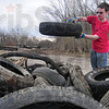 Tribune-Star/Rachel Keyes<br /> Piled it up: Rose-Hulman freshmen Brandon Naylor adds another tire to the stack as members of the community gather at Operation: Wabashiki an event sponsored by Saint Mary-of the-Woods College.