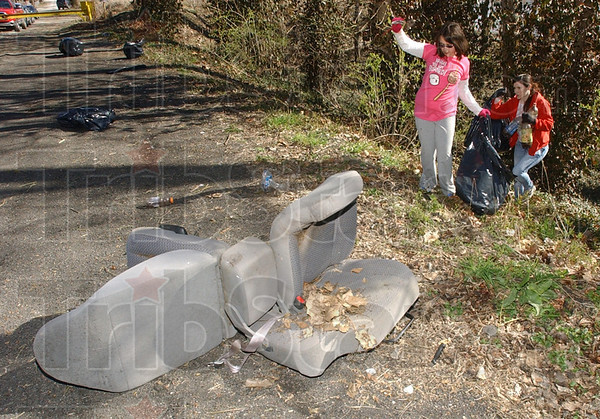 Tribune-Star/Jim Avelis<br /> Work to do: Isabella Almaghaslah and Leah McGee carry trash up to the road along the west bank of the Wabash River south of Dresser Saturday morning. Car seats, broken toys and bag after bag of household trash were collected by the handful of volunteers.