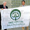 Tree City: Farrington Grove principal William Smith and Vigo County School Corp. superintendent Dan Tanoos show the Tree City USA flag to the student body after a presentation from Mayor Duke Bennett.