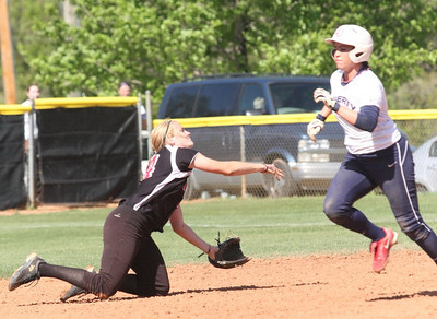 Number 14, Samantha Meenaghan, throws a runner out from her knees.