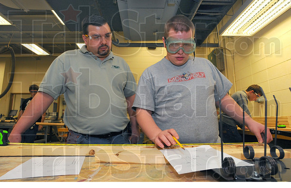 Overseer: Terre Haute South High School technology teacher Marquis Songer looks over Joshua Cegielskis' figures before giving teh go-ajead to cut the wood to sixe.