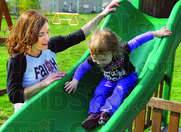 Fun: Becky Halon helps her 2-year-old daughter, Norah, down the slide in their backyard on April 8.