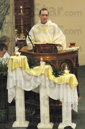 Tribune-Star/Rachel Keyes<br /> Holy scriptures: Friar Mark Weaver reads from the Gospel of John as part of the Last Supper Mass on Thursday evening at St. Joseph University Parish.