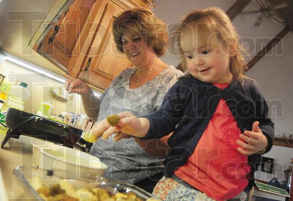 Tribune-Star/Rachel Keyes<br /> Family affair: Amy Lohman (left) gives her granddaughter Sydney Land (right) a lesson in mushroom frying.
