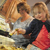 Tribune-Star/Rachel Keyes<br /> Family affair: Amy Lohman (left) gives her granddaughter Sydney Land (right) a lesson in mushroom frying.