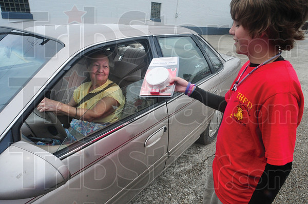 Tribune-Star/Rachel Keyes<br /> Helping dad: Holten Hodges (right) helps his fire fighting dad by giving out a  free smoke detector to Patsy Thompson (left).