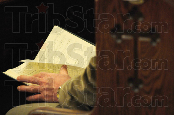 Tribune-Star/Rachel Keyes<br /> Hymns of praise: A parishioner at St. Joseph University flips through a hymnal as part of the Last Supper Mass Thursday.