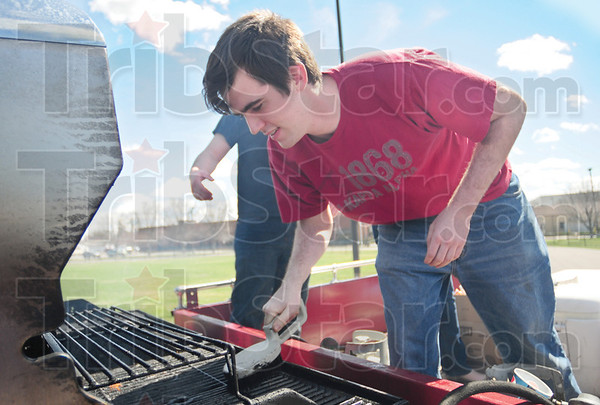 Tribune-Star/Rachel Keyes<br /> Free food: Pi Kappa Alpha member James Jeffryes cleans off the grill before tossing some more hot-dogs on at Saturday's Pi Kappa Alpha Fire Truck Pull.  The food was donated by local Kroger's and Bassler's grocery stores.