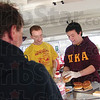 Tribune-Star/Rachel Keyes<br /> Serve it up:  Pi Kappa Alpha members Dustin Morris (left) and Stephen Collins (right) serve up some hamburgers at Saturday's Pi Kappa Alpha Fire Truck Pull.  The food was donated by local Kroger's and Baesler's grocery stores.