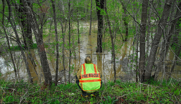 Search: Reelsville volunteer firefighter and EMT Liz Christopher watches the rapidly flowing waters of Big Walnut Creek searching for a missing kayaker