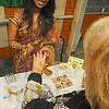 Tribune-Star/Jim Avelis<br /> Temporary art: Indiana State Unnversity student Sravya Sarvareddy applies a henna tatoo to the hand of Sherri Elledge who works in Union Hospitals' chaplains' office. The two were workers at the Union Hspital Diversity Fair Wednesday afternoon.