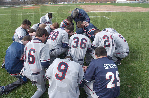 Firat things first: Faye Spetter prays with some of the Patriot team before their game with Sullivan last wek.