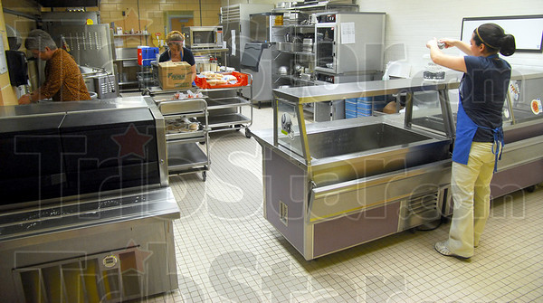 Clean up: Vigo County School Corp. employees work cleaning the kitchen of Fuqua Elementary School Monday after lunch. There is a proposal to replace the cafeteria at the school.