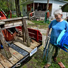 Tribune-Star/Jim Avelis<br /> Staying dry: Nida Wilson moves outdoor furniture to a trailer to be moved to high ground in Tecumseh Monday afternoon. Her husband Wayne said he looks at predicted rain amounts in order to decide whether to stay or leave their home.