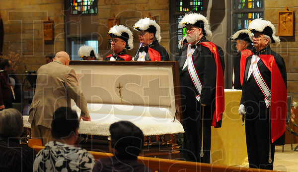 Tribune-Star/Jim Avelis<br /> Final farewell: Walter Kindrick, a longtime friend and parishioner of Father Joe Kern, leans over his casket at a wake Monday evening.