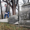 Damaged: Tribune-Star reporter Arthur Foulkes surveys the damage in the Prairie Creek Westlawn Cemetery Monday afternoon. Vandals toppled about a dozen tombstones over the past weekend.