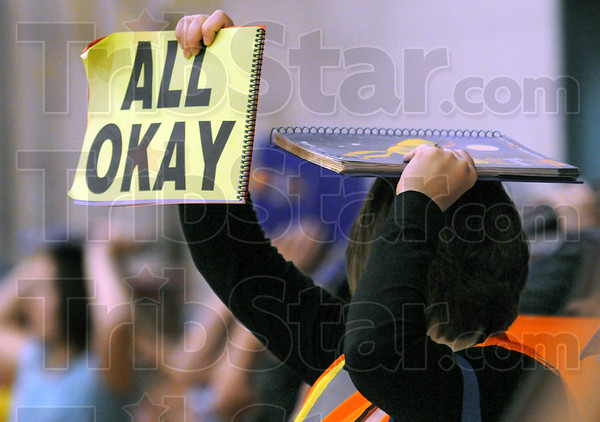 "All okay: A riley teacher holds the ""all okay"" sign during Tuesday's Great ShakeOut drill."