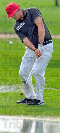 Tribune-Star/Jim Avelis<br /> Soggy day: Thomas Goss hits an iron from the sodden first fairway at Rea Park Tuesday Afternoon at the beginning of the County golf meet.