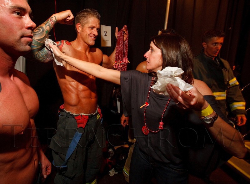 (Denver, Colorado, April 22, 2011)<br /> Jenn Corbor won the bid to help oil up the contestants, such as Brett Burke.  The 7th Annual Colorado Firefighter Celebrity Judging Event at Exdo Event Center in Denver, Colorado, on Friday, April 22, 2011.<br /> STEVE PETERSON