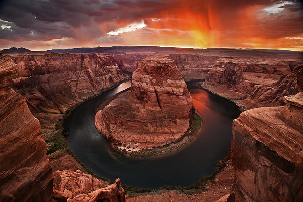 Original Post:  I spent the last couple days on a photovacation taking photos of beautiful things around northern Arizona. My photo buddy Willie and one other friend and I flew into Phoenix and drove 5 hours north to Page, Az. We arrived in the evening, just as a storm started blowing in. We immediately went over to Horseshoe Bend to see if we could get some nice photos. Although we knew that this spot was *completely* over-photographed we hoped that the storm would give us a fairly unique shot of the bend in the Colorado River. About an hour before sunset the lightning starting getting pretty close and the rain got a little heavier than we would have liked -- we sprinted back to the car to protect our gear. Luckily monsoon season in Arizona means the storms only last about 20 minutes and we were able to head back to The Bend before the sunset light started.  Fortunately for Willie and I, another storm was right behind and rolled behind Horseshoe Bend just as the sun was setting. The incoming storm created an absolutely beautiful sunset, filled with light shafts of the setting sun reflecting off the rain. The water was also calm enough to reflect the sunset in the river. We definitely had a treat of a sunset!  I rented a D700 for this trip from LensRentals.com. The D700 was absolutely amazing. With my 17-35mm lens on it I could finally go really wide and this place absolutely needed a wide angle lens. We scoped out a couple locations for this shoot and eventually decided we liked this spot because it was a little bit different than most peoples photos (who take their shots a bit to the left). I liked the two rocks on the left and right from this spot -- they point into Horseshoe Bend and frame it really nicely.   Couple other notes about Horseshoe Bend: It's right off the highway and really easy to get to. There's about a 0.75 mile walk along a sandy trail to get here and pretty much anyone except a 90 year old parent could make the trek. Once you arrive at Horsesho