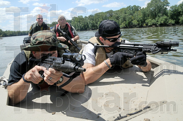 Cover fire: Terre Haute police officers Dale Blunk and David Garland prepare to lay down cover fire during a training exercise on the Wabash River Thursday afternoon. Max Winchell and Pete Horstman are in the rear of the boat.