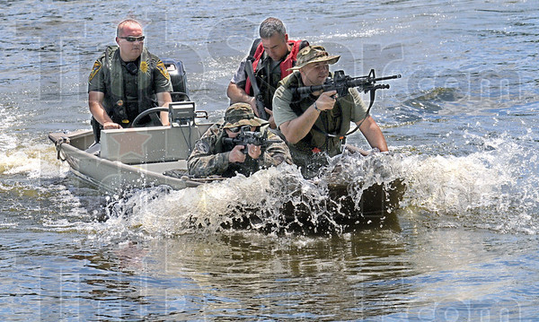 Beach assault: Conservation officers and Terre Haute Police Special Response Teams train for an amphibious assalt along the Wabash River Thursday afternoon.