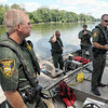 Conservation talk: Conservation officers brief members of the Terre Haute Police Department Special Response Team on the methods used to board and exit the boats during Thursday's training exercise. `