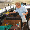 """Tribune-Star/Jim Avelis<br /> Sorting it all out: Vigo County School Corporation bus driver Doug Wilson sorts out donations to United Way's  """"Stuff the Bus"""" campaign Thursday afternoon. Hopes are to exceed last year's total of 7,000 school related items. The effort continues today with the bus locating at the Staples store from 8:00a.m. until 5:00p.m. Once gathered the supplies will be turned over to the VCSC."""