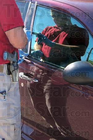 Prints: Terre Haute police detective Mike Mikuly is reflected on the side of a vehicle as he lifts fingerprints during a robbery investigation Thursday morning.
