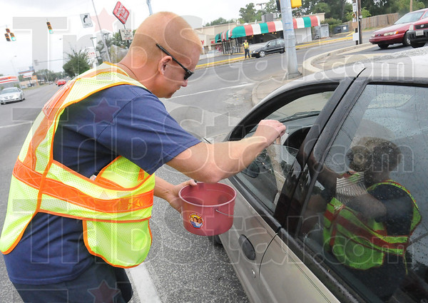 Tribune-Star/Rachel Keyes<br /> Local donations: Terre Haute firefighter Jimmy Holbert takes local donations for the Muscular Dystrophy Association Sunday afternoon.