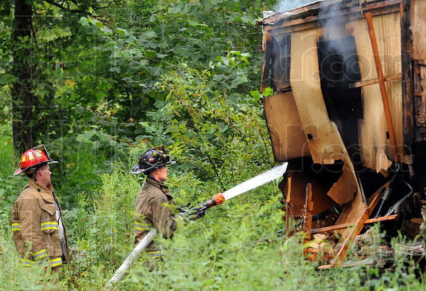 Mobile home fire: Volunteer firefighters dump water on an abandoned mobile home at a dump site near Fontanet, Indiana Friday afternoon.
