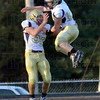 Celebration: Sullivan's #55, Jed Cox leaps onto #52, Thomas Smith after smith intercepted a pass and ran it back for a touchdown in first quarter play against Linton.