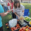 Sister act: Sisters Karyn Paulsen and Amy Daugherty work together selling produce on the square in Marshall, Illinois Friday evening.
