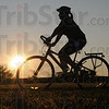 Tribune-Star/Jim Avelis<br /> Bright start: A cyclist begins her Soggy Donut ride with the sun barely up saturday morning.