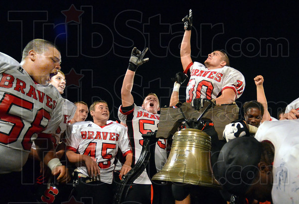 "Triumphant: South players surround the ""Bell"" after winning Saturday's annual game at Memorial Stadium by a 14-7 scpre."