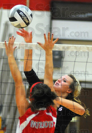 Tribune-Star/Jim Avelis<br /> Frontline: Maddie Callahan spikes the ball past the defense of Owen Valley's Kendall Hamilton in their first game Wednesday night in the Braves' gym.