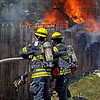 Flaming: Two Sugar Creek firefighters attempt to break through a wooden fence in the 300 block of Edwards Street in West Terre Haute Monday afternoon.