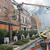 Artificial: A lift vehicle provides a lighting technician a perch from which to provide some light into the windows of the room in The Ohio Building where crews are filming a scene.