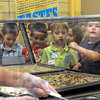 Chow time: A group of Dixie Bee Elementary School students line up for lunch during the first day of school Tuesday. Cafeteria worker Misty Talley serves the children.