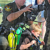 Tribune-Star/Jim Avelis<br /> Dive team: Indiana Conservation officer Max Winchell helps five-year-old Noah Black into some 70 pounds of scube gear at the National Night out.