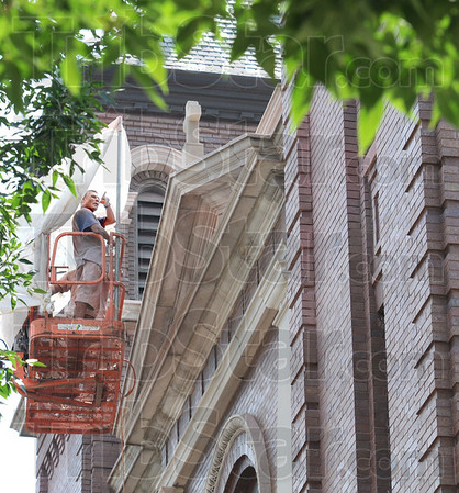 "Tuck ""point"": Nelson Rivas makes a ""point"" during his conversation with his partner David Minton as they work off a lift on the facade of St. Joseph's Catholic Church during the hottest part of the day Tuesday."