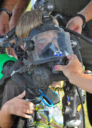 Tribune-Star/Jim Avelis<br /> Ready to go: Five-year-old Noah Black peers through Indiana Conservation officer Max Winchell's dive mask at the National Night Out. Black was there with his parents Keith and Amanda.
