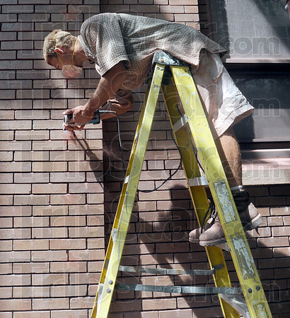 Ladder work: Dan Minton works from a step ladder Tuesday afternoon doing masonry work on St. Joseph's Catholic Church Tuesday afternoon.