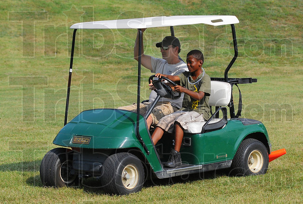 Tribune-Star/Jim Avelis<br /> Rolling along: Terre Haute city police officer Rob Pitts rides shotgun while Cordell Moshon drives a golf cart past, and over pylons during the National Night Out Tuesday evening at Fairbanks Park.