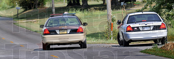 Manhunt: A Sullivan County sheriff's deputy and Indiana State Trooper confer along old US 41 near the Carlisle prison Tuesday Afternoon.