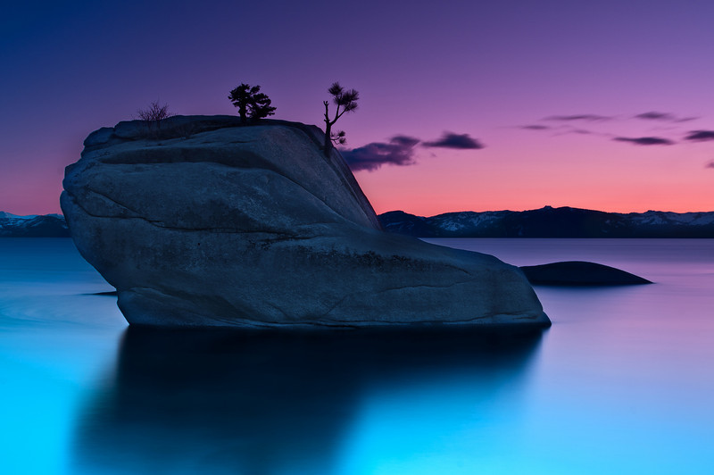 "A bunch of months ago I saw a local photographer and one of my good Flickr friends, David Shield (http://www.flickr.com/photos/davidshield/), post a photo from ""Bonsai Rock"" in Lake Tahoe. Bonsai Rock is located on the north-east side of the lake, about 45 minutes from South Lake Tahoe. If you stand on the east shore you can get spectacular sunset photos with the rock in the foreground and the sunset in the background. Ever since I saw his photo this place was on my list of things I wanted to photograph!  I attempted this photo a couple weekends ago but a storm rolled in and there was no color in the sky. I didn't even bother leaving our ski cabin to go shoot. Finally this last weekend the weather looked great and I had a chance to drive up to the north-east shore and find Bonsai Rock.  I've read a lot of blogs and viewed a lot of photos of Bonsai Rock but it was 1) harder to find and 2) harder to photograph than I expected. I spent over an hour trying to find the right location to setup the tripod and take the photo. We had a gorgeous sunset (at one point the sunset over the mountains made it look like the mountains were on FIRE!) with some great color but I couldn't keep the photo simple enough to my liking -- there were just too many rocks in the photo. I didn't realize that the water level of Lake Tahoe rises and falls. This was a medium height: some of the rocks that many other photographs show (and lead the eye into Bonsai Rock) were covered up, but a lot of the rocks behind Bonsai Rock were completely uncovered and distracted from the background. Just as I was about to leave and call it a disappointing failure I thought about taking this one last, simple, composition zooming in on the rock. The sun had set about 15 minutes earlier but the color in the sky all of a sudden lit up further west than it had earlier and a long exposure (2.5 minutes) got the silky smooth water and brought out the color in the sky! I'm quite happy with how this came out!   To find Bonsai Rock park at 39.183690 , -119.927088 and then climb down the side of the hill to 39.184844, -119.927727.   More detailed directions if you're trying to find it: The parking location is about 6.7 miles north of the highway 28/highway 50 junction. There's a small turn-out on the side of the road (on the left side of the road if you're heading from S. Lake Tahoe. If you get to what looks like a highway rest stop on the right you've gone too far. If you're coming from North Lake, it's on the right, just past Sand Harbor after the rest-stop thing on your left). If you want to throw in your GPS coordinates the parking spot is pretty much exactly at 39.183690 , -119.927088. Once you park you have to hike down a steep hill slightly north of where you park. A lot of people mentioned that it was a ""steep hike"" but I never realized that it was about a 200 foot climb down to the water. It wasn't extremely difficult to get down, but we did have to hold onto some trees/roots/rocks to make sure we didn't slip and tumble into an injury. Getting back up after the shoot was a decent workout (note: if you're going at sunset, I recommend that you DON'T forget to bring a flashlight). Bonsai Rock itself is located at 39.184844, -119.927727. Mike Wiacek (http://www.mikewiacek.com/blog/2009/08/bonsai-rock-formation-lake-tahoe/) has been so kind as to create a custom Google Maps for Bonsai Rock. Check it out at http://maps.google.com/maps/ms?ie=UTF&msa=0&msid=117078272024675730991.000471c9db1839af7e9e6.  Nikon D300s w/Nikkor 17-35mm f/2.8 ED-IF AF-S: 35mm, f/11, 2.5 minutes, ISO 100, Tripod Lee Foundation Kit Filter Holder B+W F-Pro Circular Polarizer, HiTech 0.9 Graduated ND, Hitech 0.9 ND Soft, and 0.6 ND Soft. No HDR!"